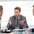 Stock Photo: Severe manager talking to his team at table