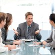 Stock Photo: Cheeful manager talking to his team at a meeting