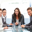 Portrait of a businesswoman with her team sitting at a table — Stock Photo #10840442