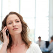 Attractive businesswoman on the phone while her team is working — Stock Photo #10840482