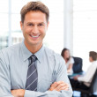Happy businessman standing in front of his team while working at — Stock Photo #10840511