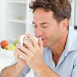 Handsome man smelling his coffee sitting in his kitchen — Stock Photo #10840629