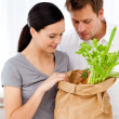 Lovely couple coming back from the market standing in the kitche — Stock Photo