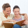 Couple smiling while looking at pictures on a photo album — Stock Photo #10840722