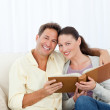 Portrait of a happy couple looking a photo album — Stock Photo #10840725