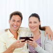 Portrait of a couple clinking glasses of red wine on the sofa — Stock Photo