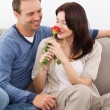 Cute woman smelling a red rose while relaxing on the sofa - Foto Stock