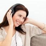 Femme souriante tout en écoute de musique sur le sofa — Photo
