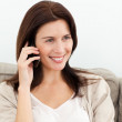 Cute woman on the phone sitting on the sofa — Stock Photo