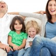 Stock Photo: Family laughing while watching television together