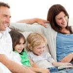 parents et enfants regardent la télévision ensemble — Photo