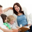 Happy parents looking at a photo album with their children — Stock Photo #10841000