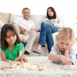 Proud parents looking at their children playing with dominoes on — Stock Photo
