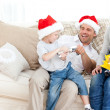 Father and son playing with a cracker on the sofa — Stockfoto