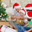 Stock Photo: Family opening christmas gifts sitting on the floor