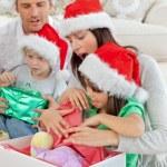 niedliche kleine Mädchen öffnen ein Weihnachtsgeschenk mit ihrer Mutter — Stockfoto
