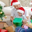 Happy family looking at the little boy opening a christmas prese — Stock Photo