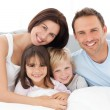Lovely family sitting together on bed — Stock Photo #10841092