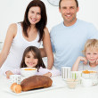 Cheerful family having breakfast together in the kitchen — Stock Photo