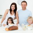 Portrait of a family having breakfast together in the kitchen — Stock Photo