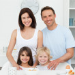 Adorable children posing with their parents in the kitchen — Stock Photo