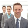 Three happy business posing in a row — Stock Photo