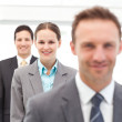 Young businesswoman posing with two businessmen in a row — Stock Photo