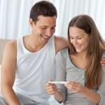 lyckliga par titta på ett graviditetstest på deras säng — Stockfoto