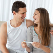Happy couple with a pregnancy test sitting on the bed — Stock Photo #10841391