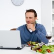 Handsome man looking at his laptop while having lunch — Stock Photo