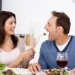 Pretty woman giving a tomato to her boyfriend while having lunch — Stock Photo