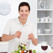 Happy man mixing a salad standing in the kitchen — Stock Photo