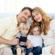 Cute family in their sofa — Stock Photo #10841859