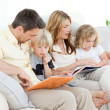 Family reading a book on their sofa - Stock Photo