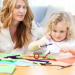 Stock Photo: Womand her daughter cutting paper