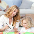 Woman and  her daughter cutting paper - Stock Photo