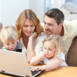 Family looking at their laptop - Stock Photo