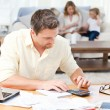 Man calculating his bills while his family are on the sofa — Stock Photo #10841977