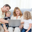 Family looking at their laptop — Stock Photo