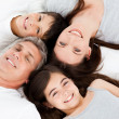 Family lying down on their bed — Stock Photo