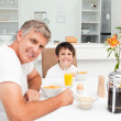 Father having his breakfast with his son - Stock Photo