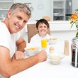 Father having his breakfast with his son — Stock Photo
