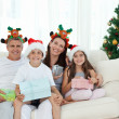 Stock Photo: Family during Christmas day looking at the camera