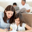 Mother helping her daughter for her homework — Stock Photo