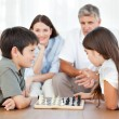 Parents looking their children playing chess — Stockfoto