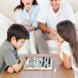 Parents looking their children playing chess — Stock Photo