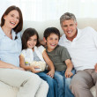 Family watching tv while they are eating popcorn — Stock Photo
