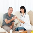 Retired man with his nurse looking at the camera — Stock Photo