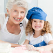 A little girl with her grandmother looking at the camera — Stock Photo #10843271