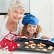 A little girl with her grandmother looking at the camera — Stock Photo #10843283
